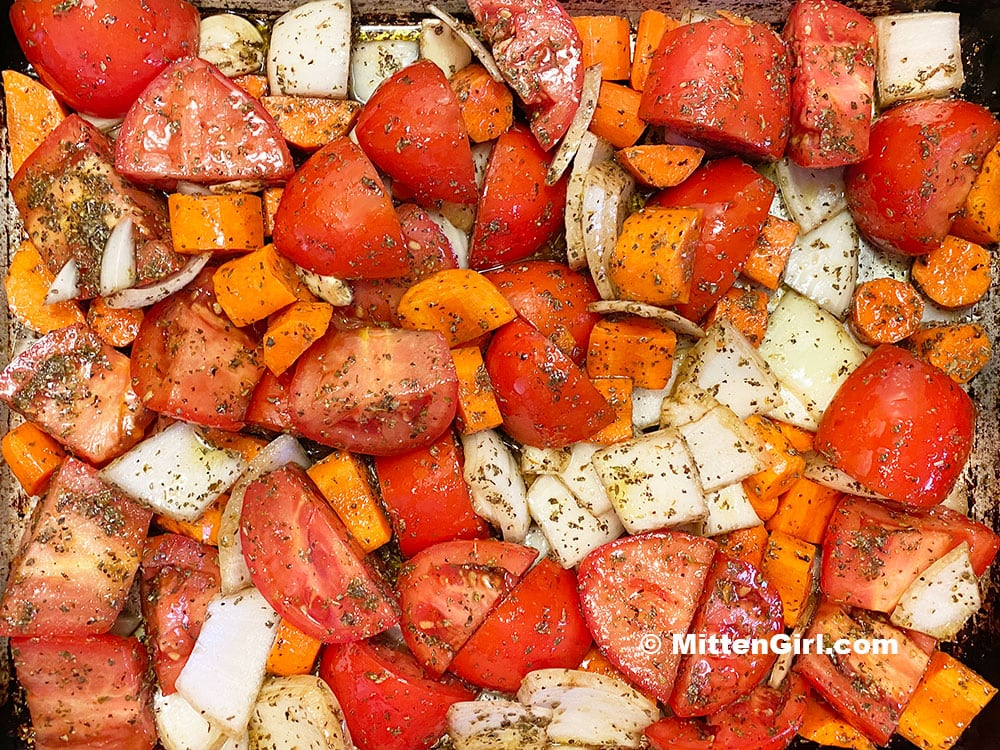 Chopped vegetables, covered in olive oil and spices, ready to go in the oven.