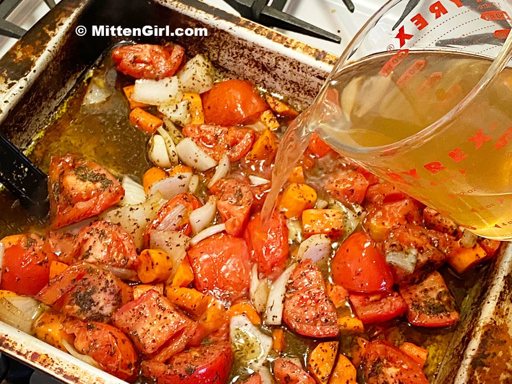 Pouring chicken broth in a pan of roasted tomatoes and other vegetables
